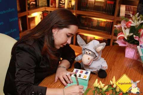 Mari Campos, do blog Pelo Mundo, autografando seu Pequeno Livro de Cruzeiros diante dos olhos xeretas de Jegueton. Imagem: Erik Pzado.