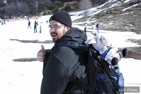 Erik Pzado com vestuário apropriado para a neve. Gorrinho, casaco e calça impermeáveis e botas para neve. Ele está sem luva, mesmo no frio, porque é primo do Chuck Norris.