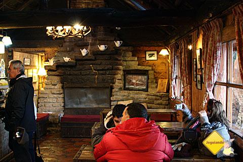 Interior da casinha de madeira, onde funciona um aconchegante café. Imagem: Erik Pzado.