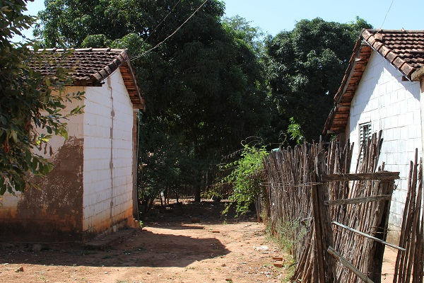 Velhas cercas de estacas, casas e o chão poeirento. Imagem: Janaína Calaça