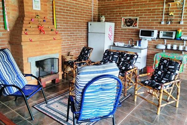 Área de convivência em um dos chalés, com geladeira, micro-ondas, pia, utensílios e mesa. Imagem: Janaína Calaça